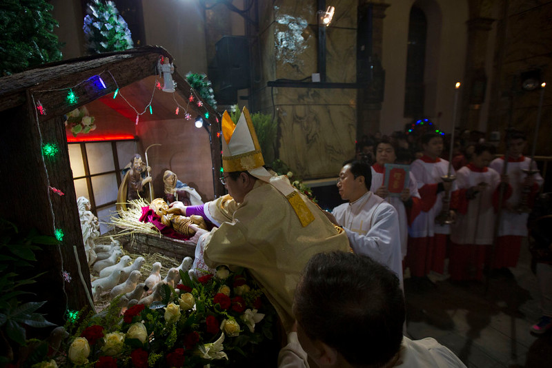. Chinese bishop Joseph Li Shan places a statue of baby Jesus in a replica of a stable as he takes part in a mass on the eve of Christmas at the South Cathedral official Catholic church in Beijing, China, Wednesday, Dec. 24, 2014. Estimates for the number of Christians in China range from the conservative official figure of 23 million to as many as 100 million by independent scholars, raising the possibility that Christians may rival in size the 85 million members of the ruling Communist Party. (AP Photo/Ng Han Guan)