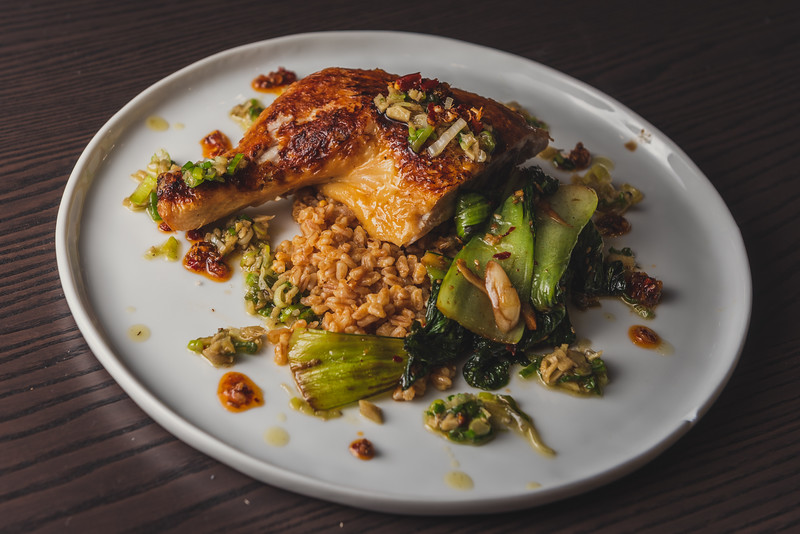 chicken under a brick with sichuan chili crisp, ginger scallion oil, farro, and bok choy