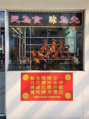 Chinese barbeque duck hanging in window with signs in Chinese