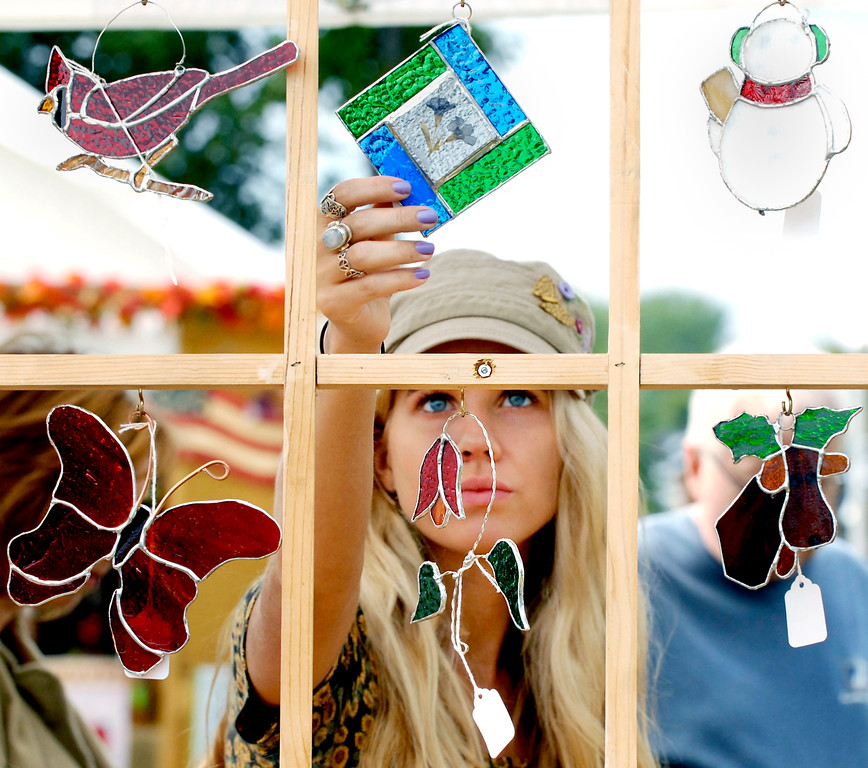 . Kelsey Wyatt looks at stained glass pieces for sale at Mike and Peggy Anthony\'s booth at the 2013 Village Peddler Festival at the Lake Metroparks Farmpark in Kirtland. The 2018 event is Sept. 15 and 16. For more information, visit www.villagepeddlerfestival.com. (News-Herald file)