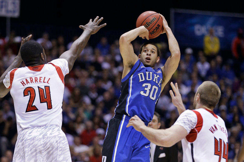 Description of . Duke's Seth Curry (30) takes a shot against Louisville's Montrezl Harrell (24) and Stephan Van Treese (44) during the first half of the Midwest Regional final in the NCAA college basketball tournament, Sunday, March 31, 2013, in Indianapolis. (AP Photo/Darron Cummings)