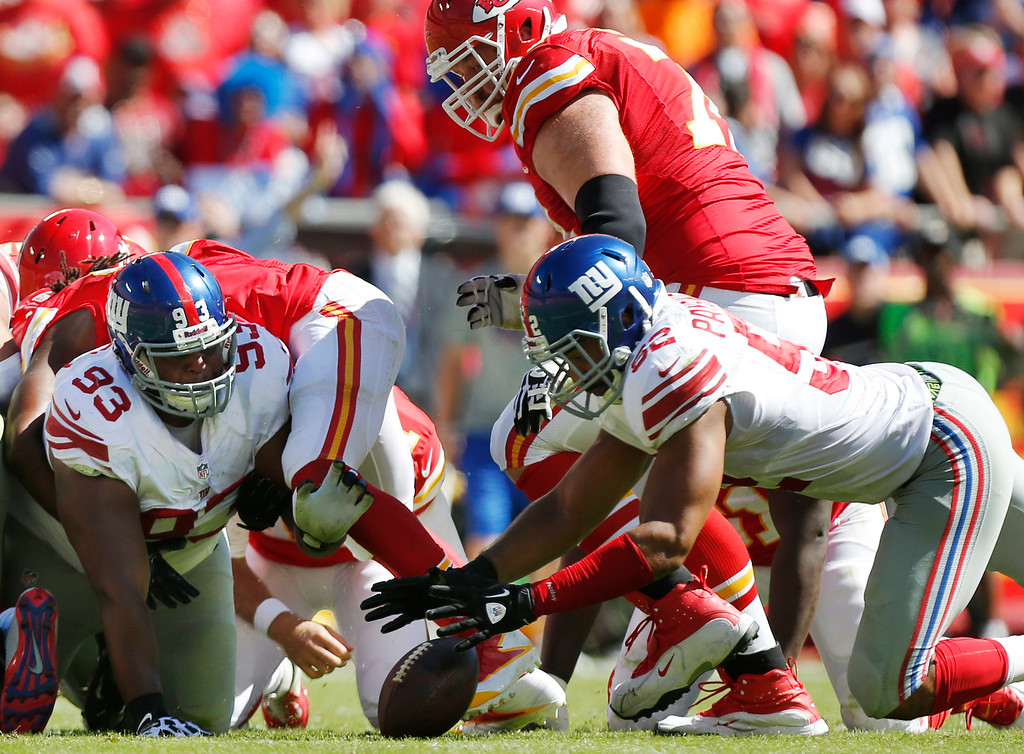 . New York Giants outside linebacker Spencer Paysinger (52) recovers a fumbled ball with help from defensive tackle Mike Patterson (93) during the first half of an NFL football game against the Kansas City Chiefs at Arrowhead Stadium in Kansas City, Mo., Sunday, Sept. 29, 2013. (AP Photo/Ed Zurga)