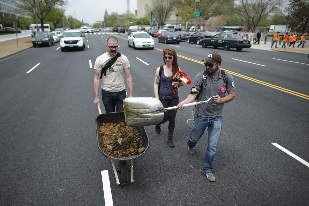 ". (L-R) Farhad Ebrahimi of Boston, Virginia Leavell of the District of Columbia and David Turnbull of San Francisco scoop horse manure up from the middle of Independence Avenue after members of the Cowboy and Indian Alliance rode horseback while demonstrating against the proposed Keystone XL pipeline April 22, 2014 in Washington, DC. As part of its ""Reject and Protect\"" protest, the Cowboy and Indian Alliance is organizing a weeklong series of actions by farmers, ranchers and tribes to show their opposition to the pipeline.  (Photo by Chip Somodevilla/Getty Images)"