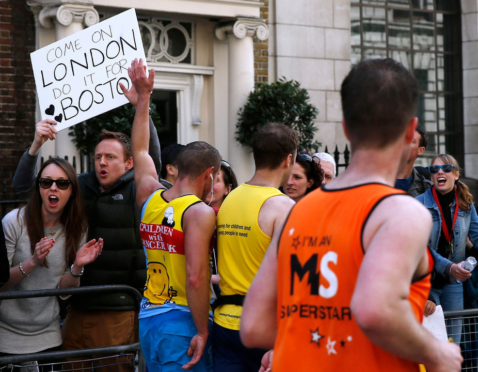 . Spectators hold a placard in support of Boston as runners pass during the London Marathon in central London April 21, 2013. Undaunted by the Boston Marathon bombings, big crowds lined the route of London \'s mass road race on Sunday to cheer on around 36,000 runners, many of whom wore black ribbons to remember the dead and wounded. REUTERS/Eddie Keogh