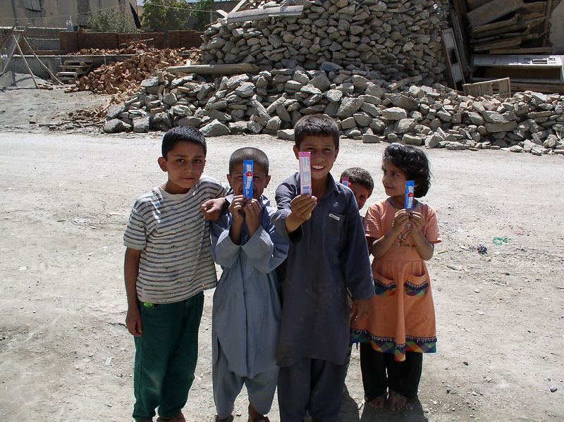 """My neighborhood friends with """"Airheads"""" candy. Notice the piles of rubble in the background."""
