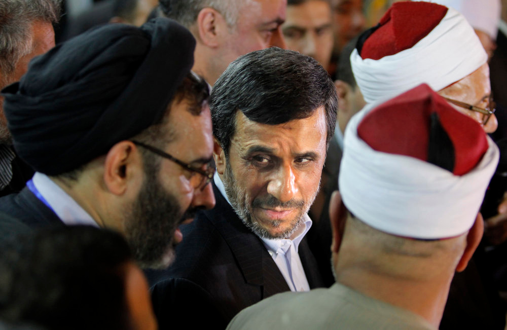 Description of . Iran's President Mahmoud Ahmadinejad, center, attends a press conference with Egyptian Sunni clerics at Al-Azhar headquarters in Cairo, Egypt, Tuesday, Feb. 5, 2013. Egypt's most prominent Muslim cleric, the sheik of Al-Azhar, has warned Iranian President Mahmoud Ahmadinejad against interfering in Arab Gulf countries or trying to spread Shiite influence. Ahmadinejad, on a landmark visit to Egypt on Tuesday, received an uneasy reception from Ahmed el-Tayeb at Al-Azhar, the Sunni Muslim world's foremost Islamic institution. (AP Photo/Amr Nabil)