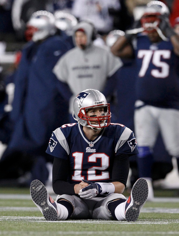 Description of . New England Patriots quarterback Tom Brady sits on the turf in front of head coach Bill Belichick after an incomplete pass on a fourth down try in the fourth quarter against the Baltimore Ravens in the NFL AFC Championship football game in Foxborough, Massachusetts, January 20, 2013.  REUTERS/Jim Young