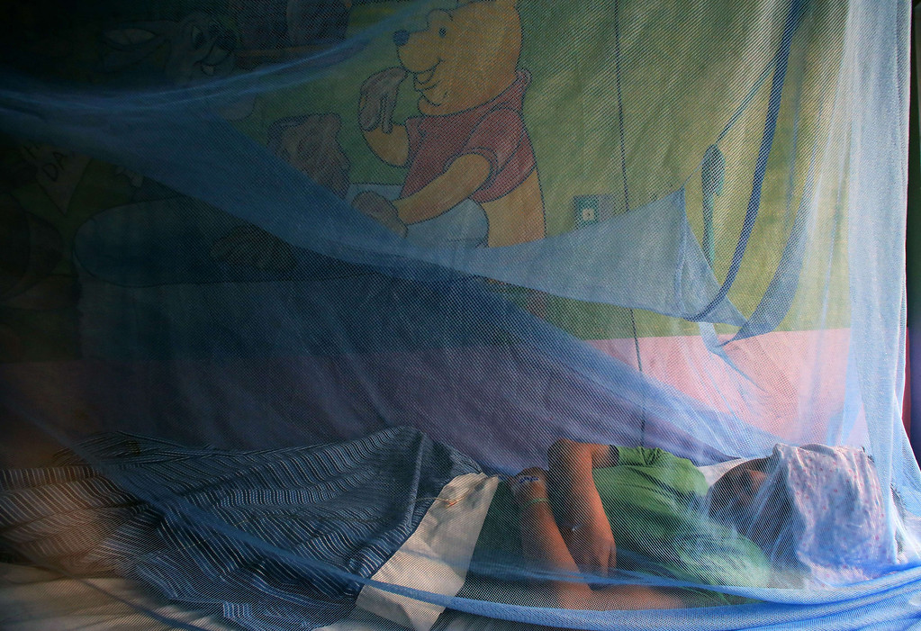 ". Kevin Flores, 11, remains under a mosquito net as he is being treated for dengue fever, at ""La Mascota\"" hospital in Managua, on October 30, 2013. The Nicaraguan government issued a health red alert as a dengue fever epidemic has killed 14 people so far this year and infected more than 5,000 individuals. Dengue, transmitted by the Aedes aegypti mosquito, occurs in Central America mostly during its rainy season from May to November. The disease causes fever, muscle and joint ache as well as potentially fatal dengue hemorrhagic fever and dengue shock syndrome. Inti Ocon/AFP/Getty Images"