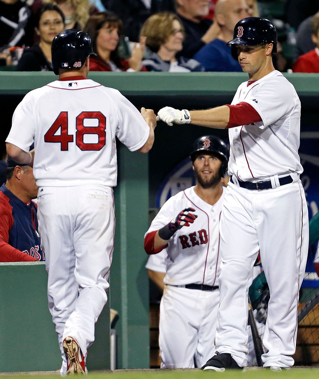 . Boston Red Sox Mike McCoy (48) is greeted at the dugout after scoring on a WIll Middlebrooks double, for the go-ahead run in the seventh inning of an exhibition baseball game against the Minnesota Twins in Fort Myers, Fla., Thursday, March 27, 2014. (AP Photo/Gerald Herbert)