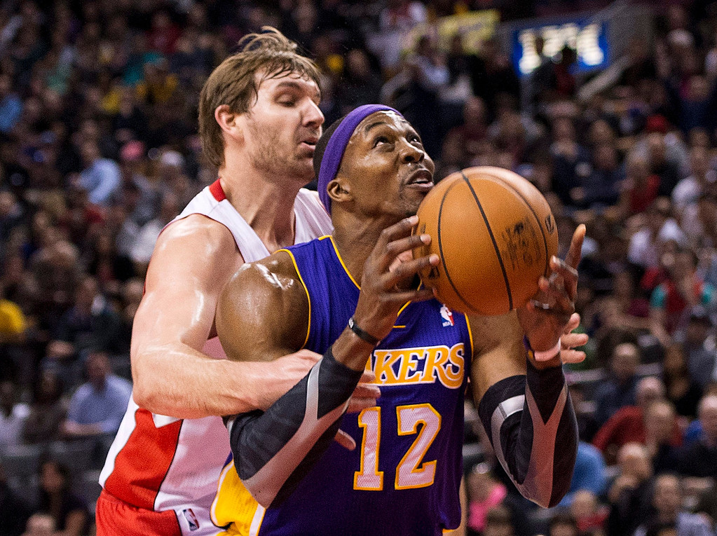 . Los Angeles Lakers forward Dwight Howard, right, drives past Aaron Gray, left, during first half NBA basketball action in Toronto on Sunday Jan. 20, 2013. (AP Photo/THE CANADIAN PRESS,Nathan Denette)