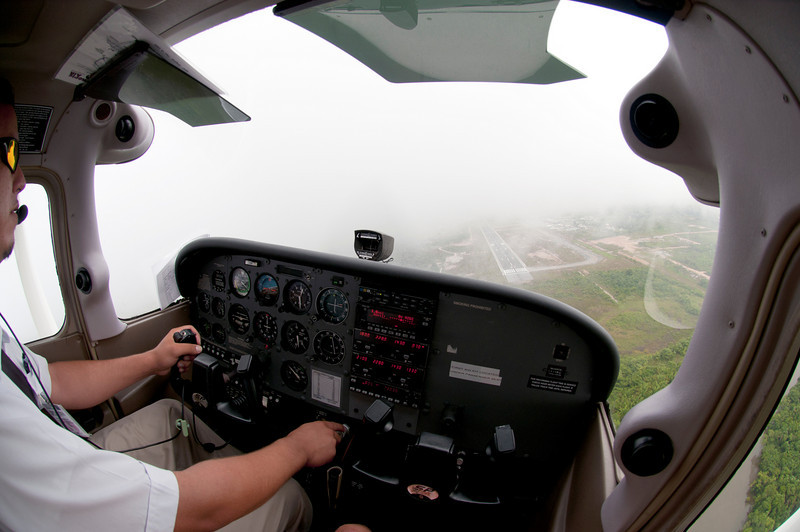 Tropic Air looking for the runway through a break in the clouds. Belize City.