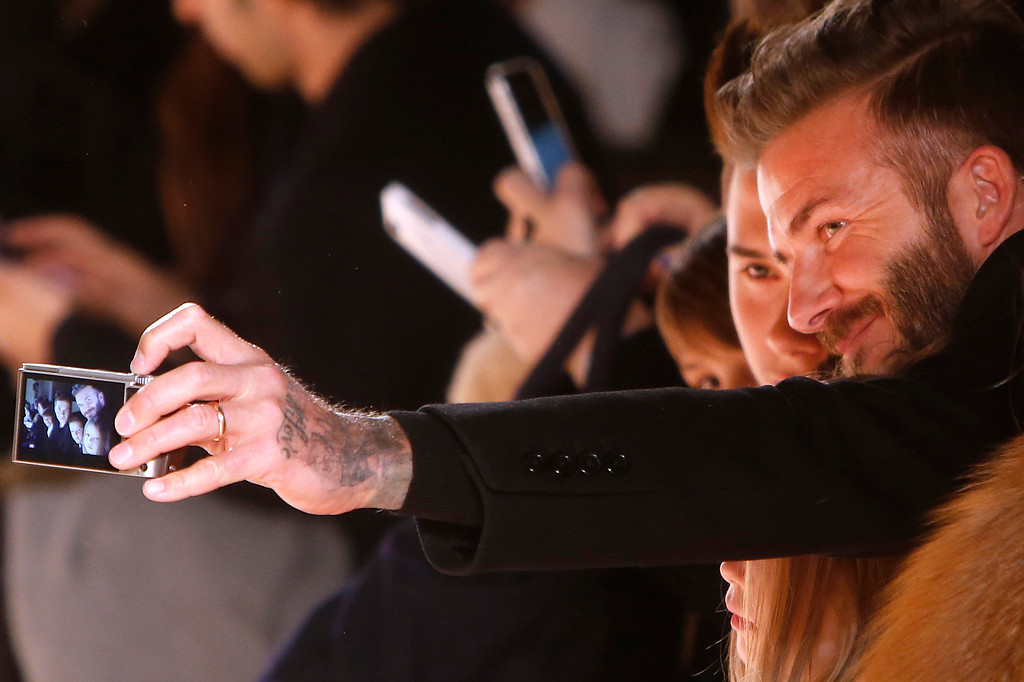 . British soccer star David Beckham takes a photo with his children in the front row after the Victoria Beckham Fall 2015 collection show during Fashion Week, Sunday, Feb. 15, 2015, in New York. (AP Photo/Jason DeCrow)