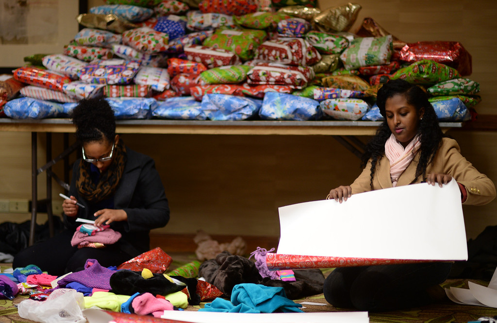 ". DENVER, CO. DECEMBER 21: Mahder Ferede, 19, of Aurora, left, and Sara Dessie, 17, of Denver are  wrapping Christmas gift during the annual Father Woody Christmas Party in Denver, Colorado December 21, 2013. In advance of handing out 5,000 gifts, volunteers are doing a ""wrapping party\"" at the Sheraton Denver Downtown Hotel. (Photo by Hyoung Chang/The Denver Post)"