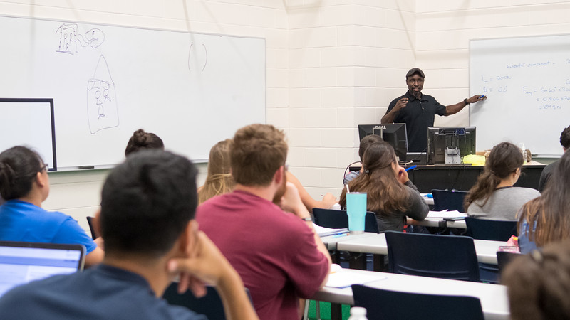 Dr. Toyin Ajisafe engages students while reviewing an exam during his Biomechanics lecture.