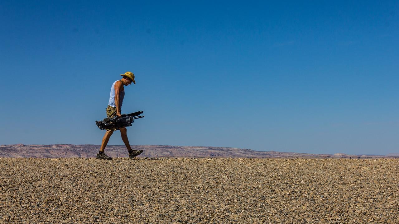 Videographer Jeffrey Lehmann lugging his gear in southern Utah