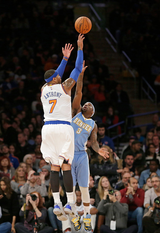 . New York Knicks forward Carmelo Anthony (7) shoots over the defense of Denver Nuggets guard Ty Lawson (3) in the first half of an NBA basketball game at Madison Square Garden in New York, Sunday, Nov. 16, 2014.  Anthony and J.R. Smith each had 28 points as the Knicks defeated the Nuggets 109-93. (AP Photo/Kathy Willens)