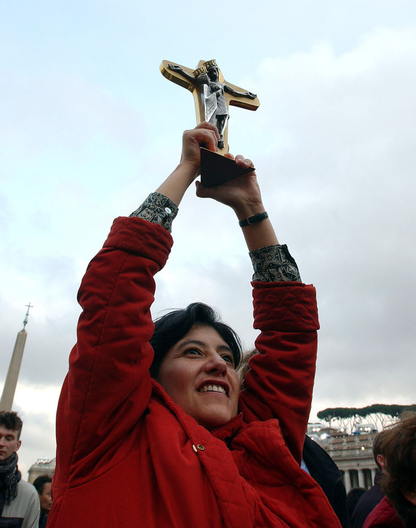. A woman displays a crucifix as German Cardinal Joseph Ratzinger appears on the balcony of St.Peter\'s Cathedral as Pope Benedict XVI at the end of the second day of the conclave April 19, 2005 in St. Peter\'s Square in Vatican City. German Cardinal Joseph Ratzinger, Pope Benedict XVI, was elected the 265th pope and will lead the world\'s 1 billion Catholics.  (Photo by Marco Di Lauro/Getty Images)