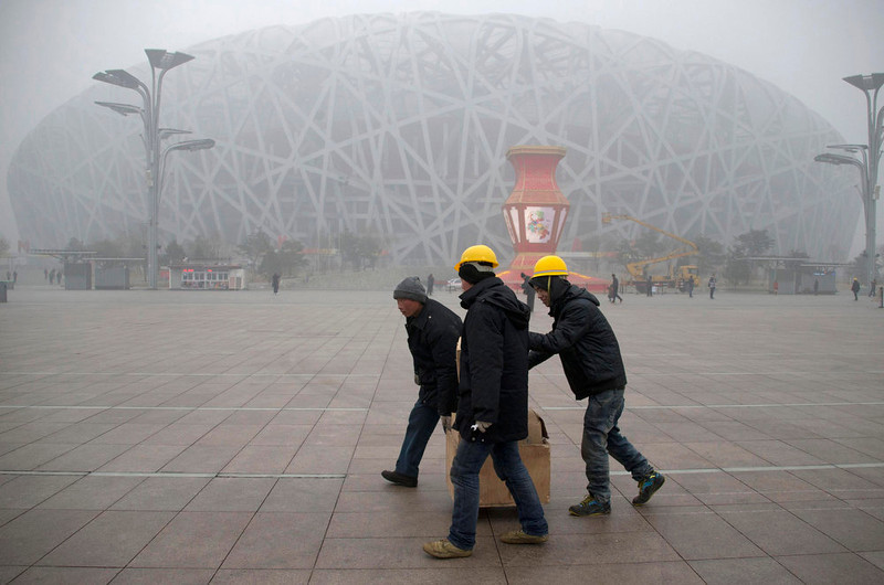 ". Workers carrying boxes walk past the fog-enveloped National Stadium, also known as the ""Bird\'s Nest\"", at Beijing Olympic park, on a foggy day in Beijing, January 31, 2013. Beijing temporarily shut down 103 heavily polluting factories and took 30 percent of government vehicles off roads to combat high air pollution, state media reported on Tuesday, but the capital\'s air remained smoggy despite the measures. REUTERS/China Daily"