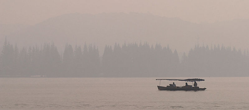 A boat on the lake in the morning fog.