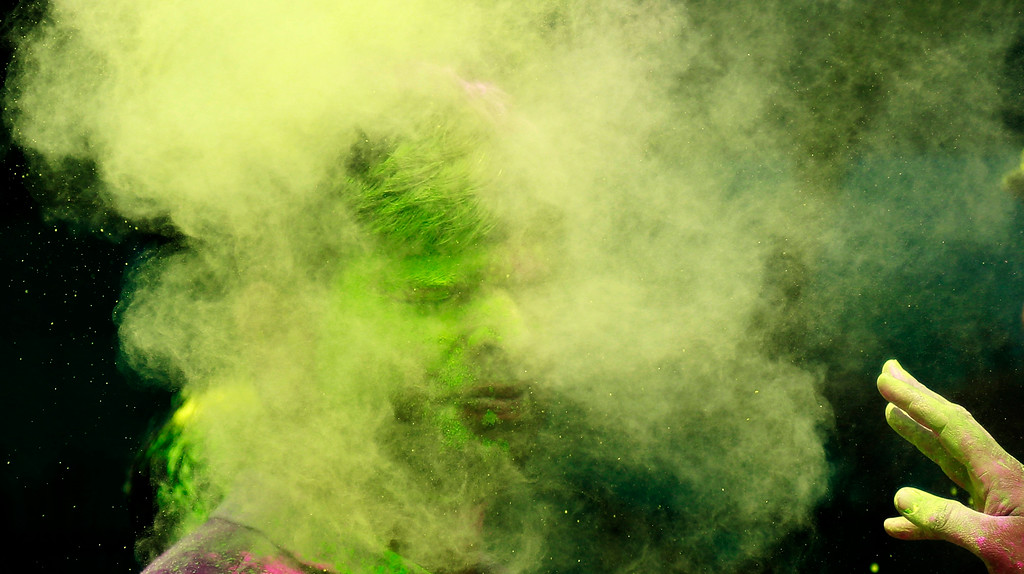 . An Indian man throws colored powder on another as they celebrate Holi, the Hindu festival of colors, in Mumbai India, Monday, March 17, 2014. The festival heralds the arrival of spring. (AP Photo/ Rafiq Maqbool)