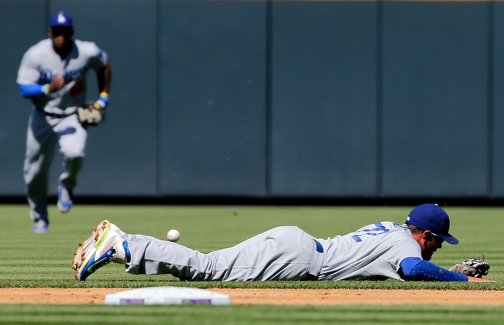 . The ball bounces past Los Angeles Dodgers shortstop Miguel Rojas (72) during the first inning of a baseball game against the Colorado Rockies, Wednesday, Sept. 17, 2014, in Denver. (AP Photo/Jack Dempsey)