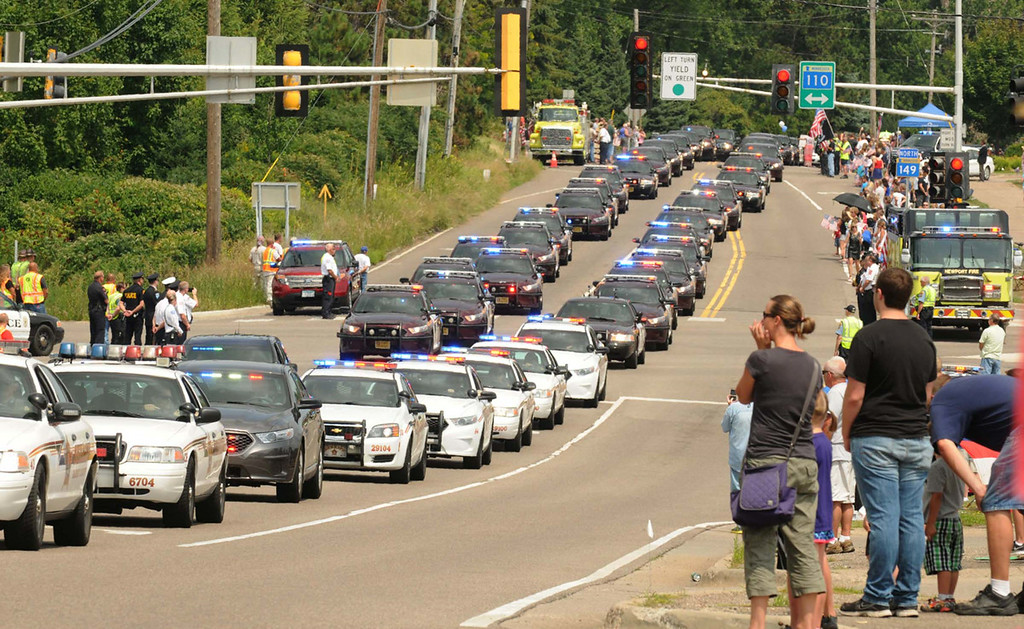 . Hundreds of law enforcement squad cars stream along Dodd Road at the intersection of Highway 110 in Mendota Heights as they make their way to the burial service for Mendota Heights police officer Scott Patrick at Acacia Park Cemetery.   (Pioneer Press: Scott Takushi)