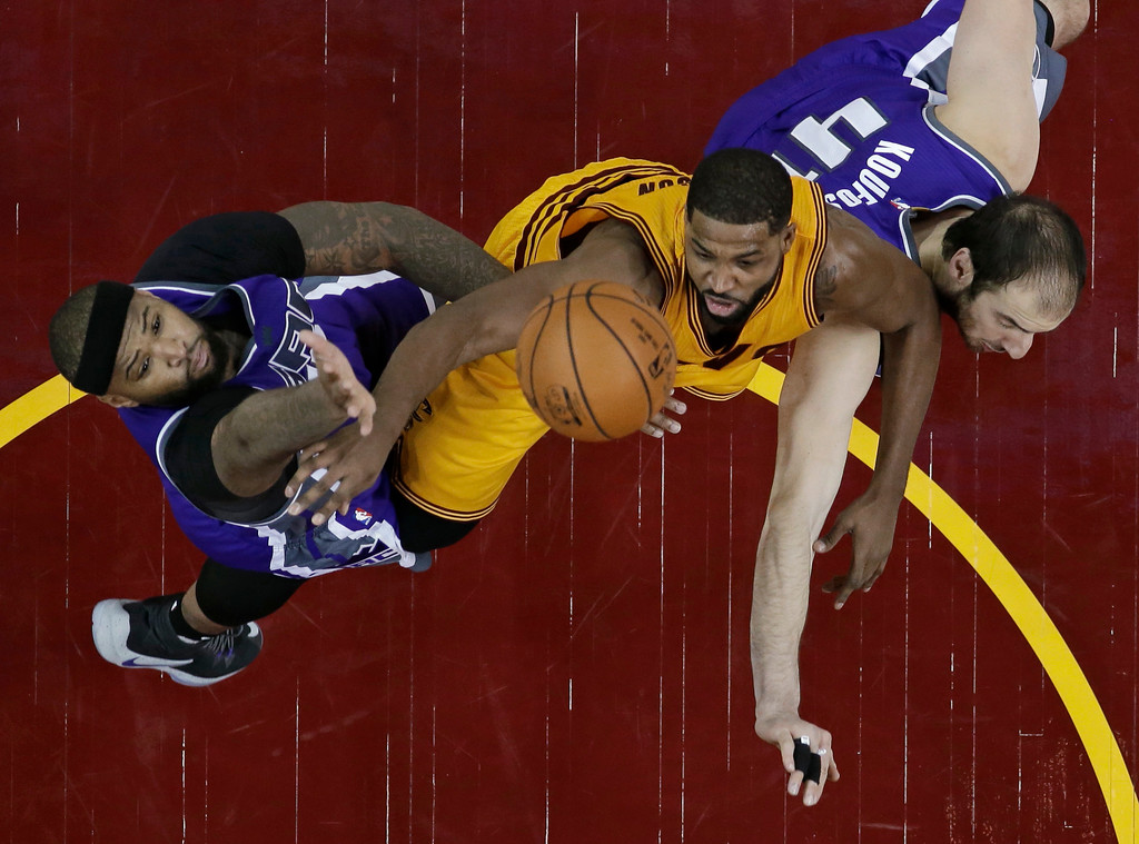 . Sacramento Kings\' DeMarcus Cousins, left, and Kosta Koufos, right, put pressure on Cleveland Cavaliers\' Tristan Thompson during the second half of an NBA basketball game, Wednesday, Jan. 25, 2017, in Cleveland. The Kings won 116-112 in overtime. (AP Photo/Tony Dejak)