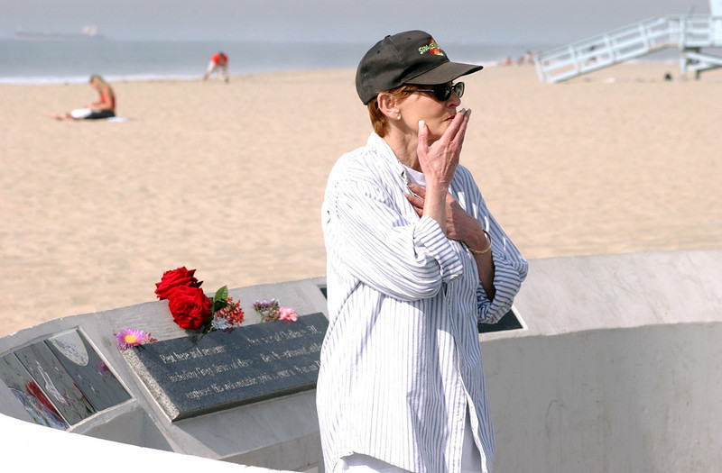 . Barbara Dellerson of Hermosa Beach, Calif., reacts after seeing fresh flowers on the memorial to Challenger shuttle astronaut Greg Jervis, also of Hermosa Beach, and his crew who were lost in the 1986 space shuttle explosion, Saturday, Feb. 1, 2003, in Hermosa Beach, Calif.  Flowers were being placed at the memorial throughout the day in memory of the seven Columbia astronauts who perished when their shuttle disintegrated upon re-entry. (AP Photo/Rene Macura)