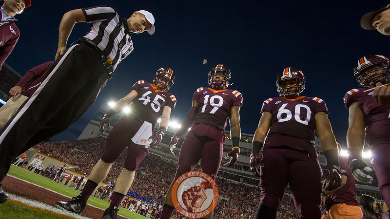Game captains Sam Rogers (45), Chuck Clark (19), and Woody Baron (60) watch the coin toss before kickoff. (Mark Umansky/TheKeyPlay.com)