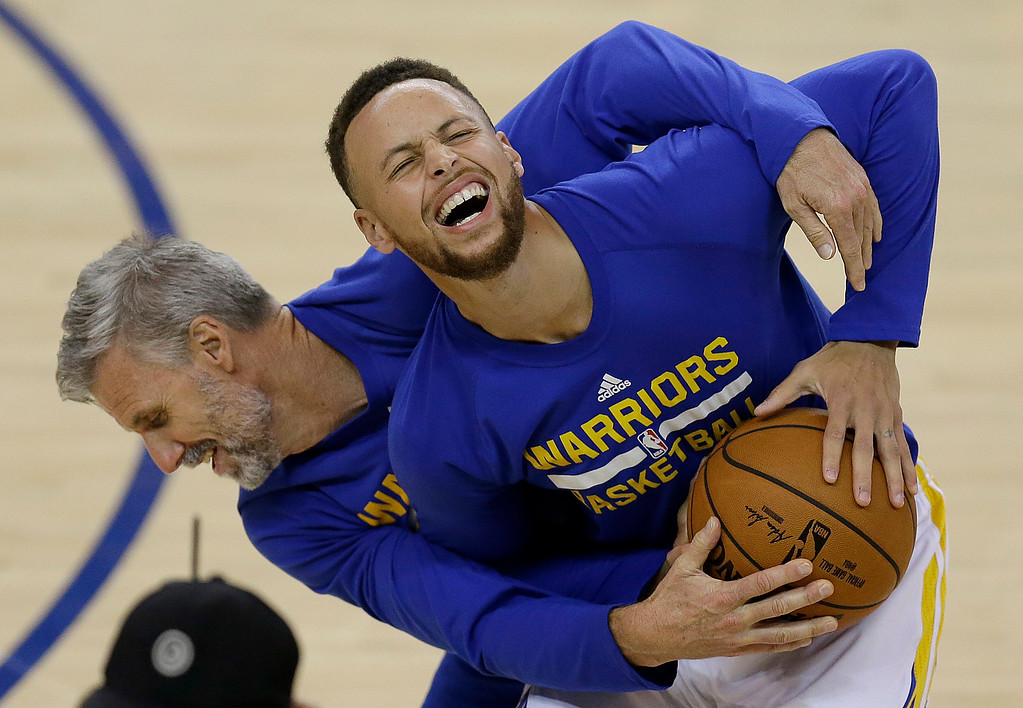 . Golden State Warriors guard Stephen Curry, right, laughs while warming up with assistant coach Bruce Fraser before Game 5 of basketball\'s NBA Finals between the Warriors and the Cleveland Cavaliers in Oakland, Calif., Monday, June 12, 2017. (AP Photo/Ben Margot)
