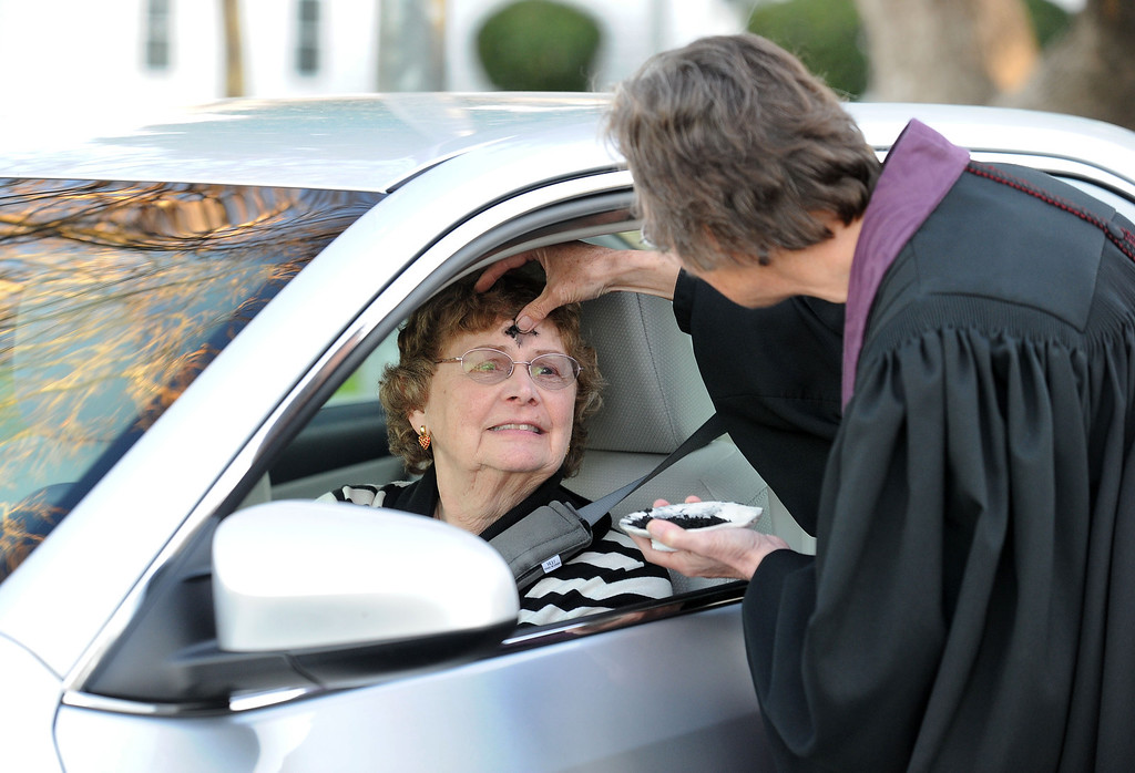 . The Rev. Christy Parks-Ramage, right, with the First Congregational Church of Antioch, gives ashes to Lois Zollars, of Pittsburg, during the drive-by prayers and the imposition of ashes for Ash Wednesday held in Pittsburg, Calif., on Wednesday, Feb. 13, 2013. The drive-through Ash Wednesday was held by the East County Shared Ministry. (Doug Duran/Staff)
