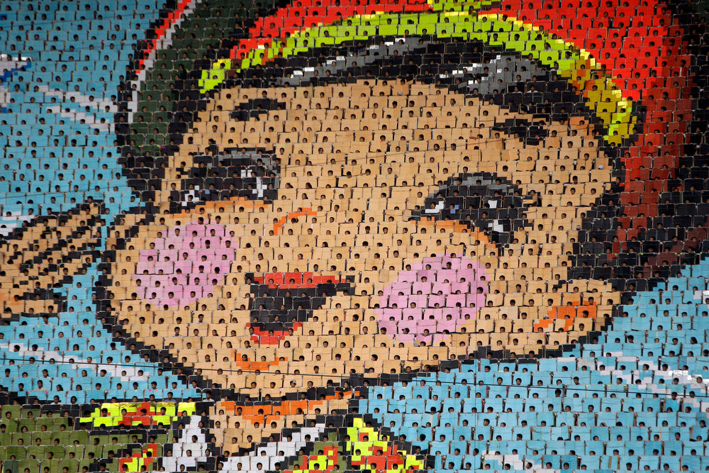 Description of . Thousands of North Koreans turn colored cards to form an image of a saluting child in military uniform during a