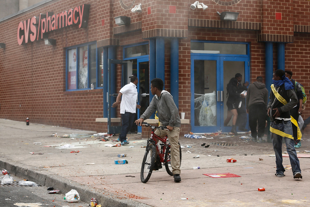 . BALTIMORE, MD - APRIL 27:  People stand outside a damaged CVS pharmacy near the intersection of Pennsylvania Avenue and North Avenue, April 27, 2015 in Baltimore, Maryland. Riots have erupted in Baltimore following the funeral service for Freddie Gray, who died last week while in Baltimore Police custody. (Photo by Drew Angerer/Getty Images)