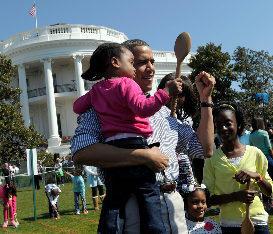 . President Barack Obama hold a child after participated in the annual Easter Egg Roll on the South Lawn of the White House in Washington, Monday, April 1, 2013. (AP Photo/Susan Walsh)