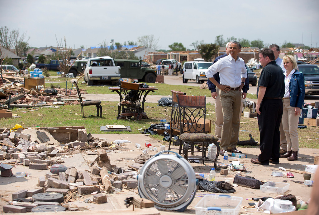 . President Barack Obama views the devastation of Moore, Okla., with Mayor Glenn Lewis, second from left in black shirt, and Oklahoma Gov. Mary Fallin, right, Sunday, May 26, 2013, in Moore, Okla. The town was devastated the week before by a massive tornado and severe weather. (AP Photo/Carolyn Kaster)