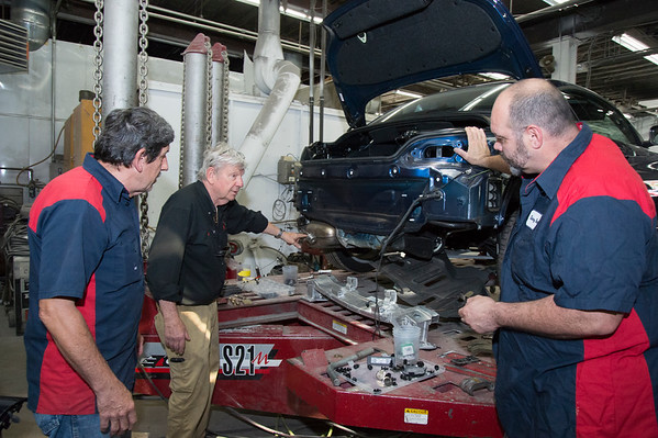 08/12/19 Wesley Bunnell | Staff Gene Herms, Bob Story and Doug Dedomonicis looks over the repair work needed on a 2017 BMW in the shop after an accident.