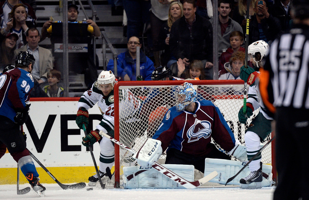 . Goalie Semyon Varlamov (1) of the Colorado Avalanche keeps an eye on the puck as Nino Niederreiter (22) of the Minnesota Wild comes from the back of the net during the first period of action. The Colorado Avalanche hosted the Minnesota Wild in the first round of the Stanley Cup Playoffs at the Pepsi Center in Denver, Colorado on Saturday, April 19, 2014. (Photo by John Leyba/The Denver Post)