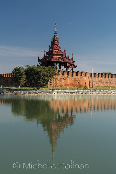 Reflection of old palace walls on the moat surrouding it in Mandalay, Myanmar