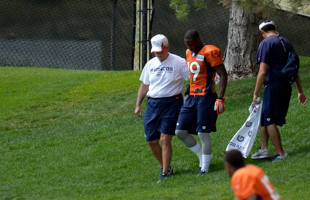 . Denver Broncos wide receiver Lamaar Thomas (19) walks off with head trainer Steve Antonopulos after going down with an injury after catching a pass during practice August 23, 2013 at Dove Valley (Photo by John Leyba/The Denver Post)