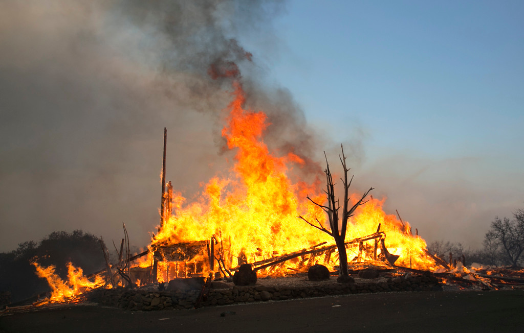 . Flames from a wildfire consume a home Monday, Oct. 9, 2017, east of Napa, Calif. The fire is one of several burning across Northern California\'s wine country. (AP Photo/Rich Pedroncelli)
