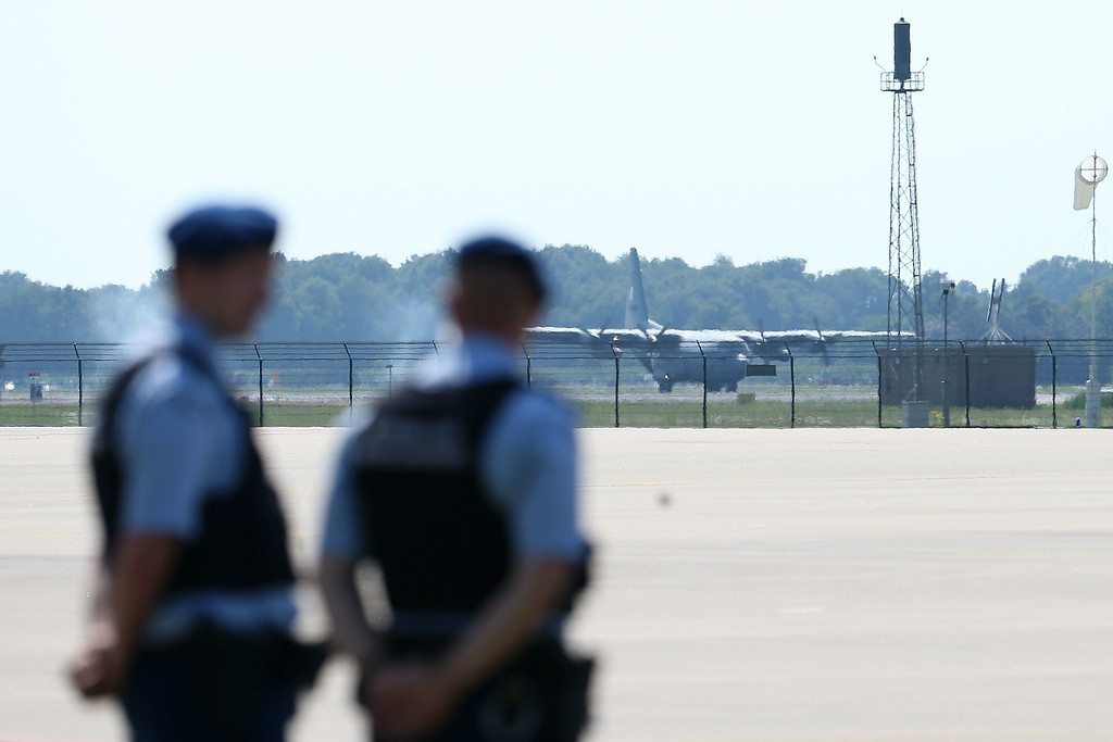 . Local Dutch police watch as a plane touches down carrying the bodies of crash victims from Malaysia Airlines flight MH17 on July 23, 2014 at Eindhoven Airport, Netherlands. Today the people of the Netherlands are holding a national day of mourning. Malaysian Airlines flight MH17 was traveling from Amsterdam to Kuala Lumpur when it crashed in eastern Ukraine killing all 298 passengers. The aircraft was allegedly shot down by a missile and investigations continue to find the perpetrators of the attack.  (Photo by Peter Macdiarmid/Getty Images)