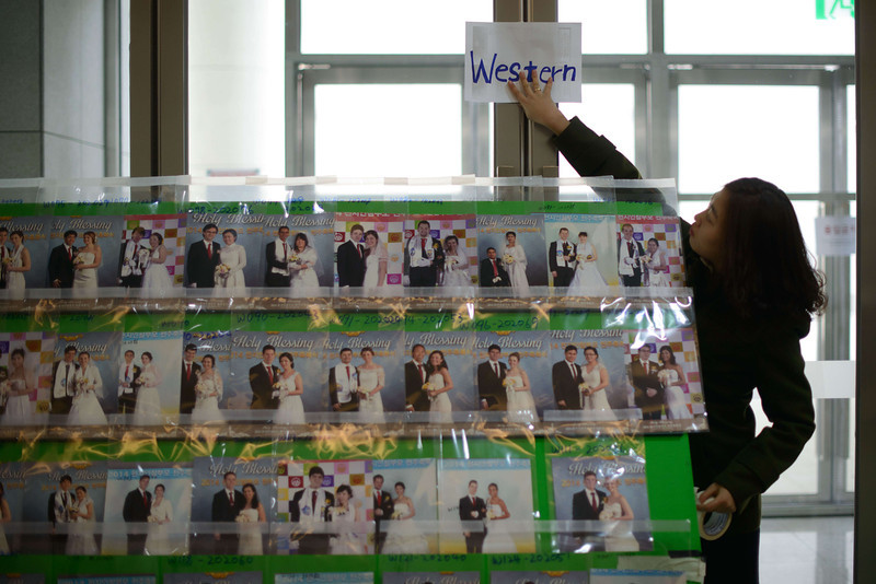 ". A woman posts a sign above wedding photos at a mass wedding event held by the Unification Church in Gapyeong on February 12, 2014. Unification Church members forming 2500 couples from 52 countries were married in a mass wedding in South Korea -- only the second such event since the death of their ""messiah\"" and controversial church founder Sun Myung Moon. (ED JONES/AFP/Getty Images)"