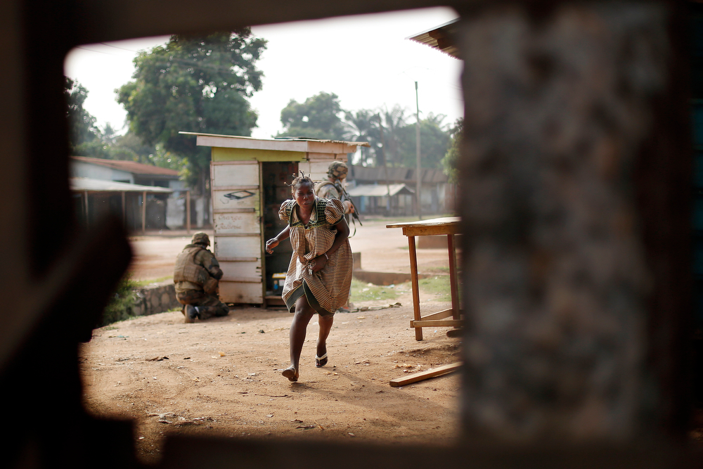 . A woman runs for cover as heavy gunfire erupts in the Miskin district of Bangui, Central African Republic, Monday Feb. 3, 2014. In what a French soldier on the scene describes as the heaviest exchange of fire he\'d seen since early December 2013, Muslim militias engaged Burundi troops who returned fire. A third source of firing remained unidentified. Fighting between Muslim Seleka militias and Christian anti-Balaka factions continues as French and African Union forces struggle to contain the bloodshed. (AP Photo/Jerome Delay)