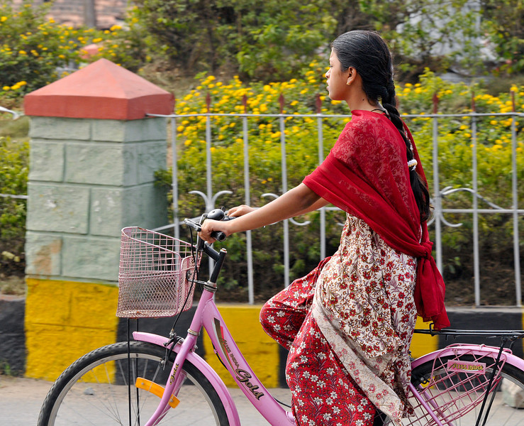 """Street scenes. A young woman on a pink """"Miss India"""" bike."""