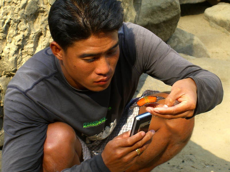 Man Holding a Butterfly and Mobile Phone - Vang Vieng, Laos