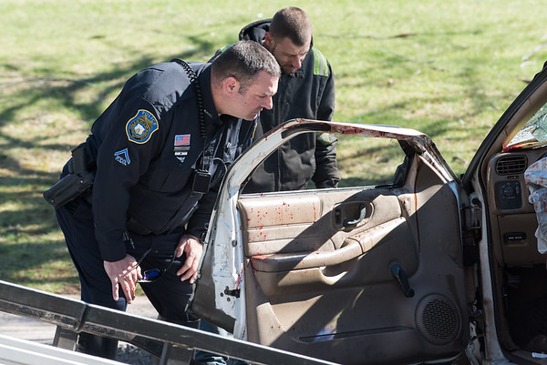 04/10/19 Wesley Bunnell | Staff Ofc. Peter Scirpo examines the inside of a Chevrolet S10 with what appears to be blood covering the door and airbag following an accident on Wednesday afternoon on Ellis St. The truck came to rest on its roof and needed to be rolled back onto its wheels before being towed.