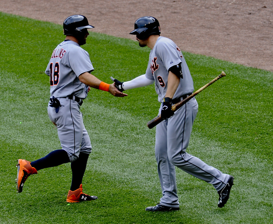 . Detroit Tigers Tyler Collins gets high-fived by Detroit Tigers Nick Castellano after he scored on a hit by Detroit Tigers  J.D. Martinez during the fourth inning of a baseball game against the Chicago White Sox in Chicago on Sunday, June 7,  2015.  (AP Photo/Matt Marton)