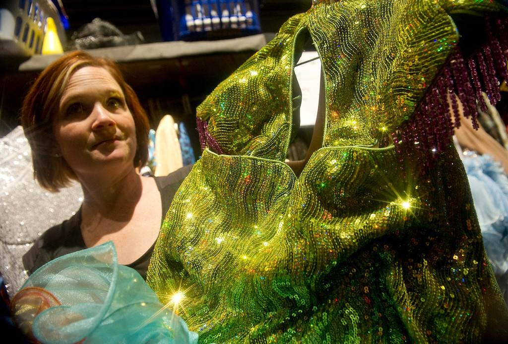 """. Wardrobe supervisor Gillian Austin holds one of the  sequined dresses backstage at the Buell Theatre for the colorful production of \""""Priscilla Queen of the Desert The Musical\"""" on Thursday September 5, 2013. There are over 500 Tony Award winning costumes.   (Photo By Cyrus McCrimmon/The Denver Post )"""