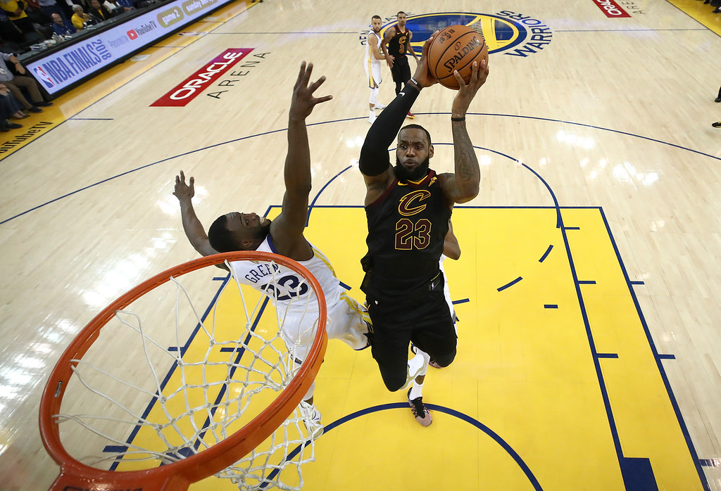 . Cleveland Cavaliers forward LeBron James, right, shoots against Golden State Warriors forward Draymond Green during the second half of Game 1 of basketball\'s NBA Finals in Oakland, Calif., Thursday, May 31, 2018. The Warriors won 124-114 in overtime. (Ezra Shaw/Pool Photo via AP)