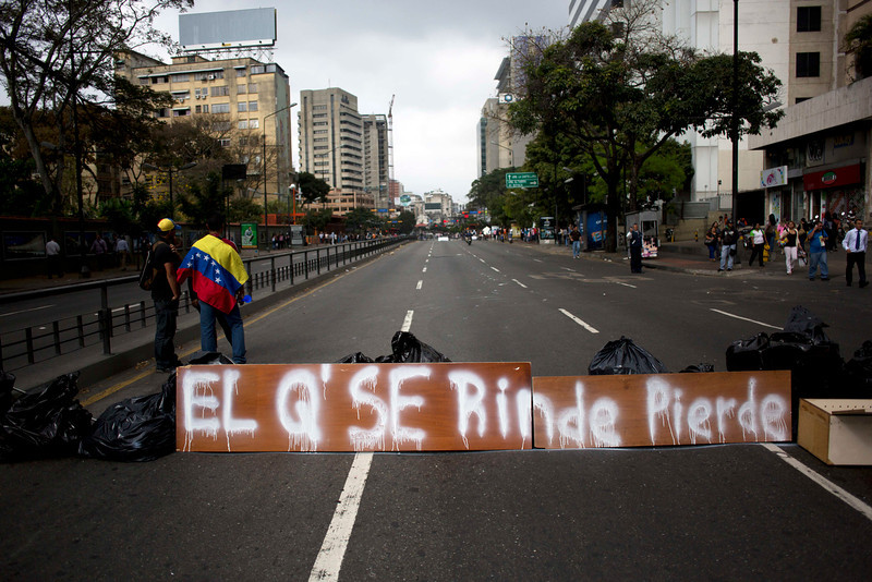". People gather next to a barricade with a sign that reads in Spanish: ""He who gives up, loses\""  in Caracas, Venezuela, Monday, Feb. 24, 2014. Since Feb. 12, opponents of President Nicolas Maduro have been staging countrywide protests that the government says have resulted in scores of deaths and more than one hundred injuries. The demonstrators blame Maduro\'s administration for the country\'s high crime rate and economic troubles. (AP Photo/Rodrigo Abd)"